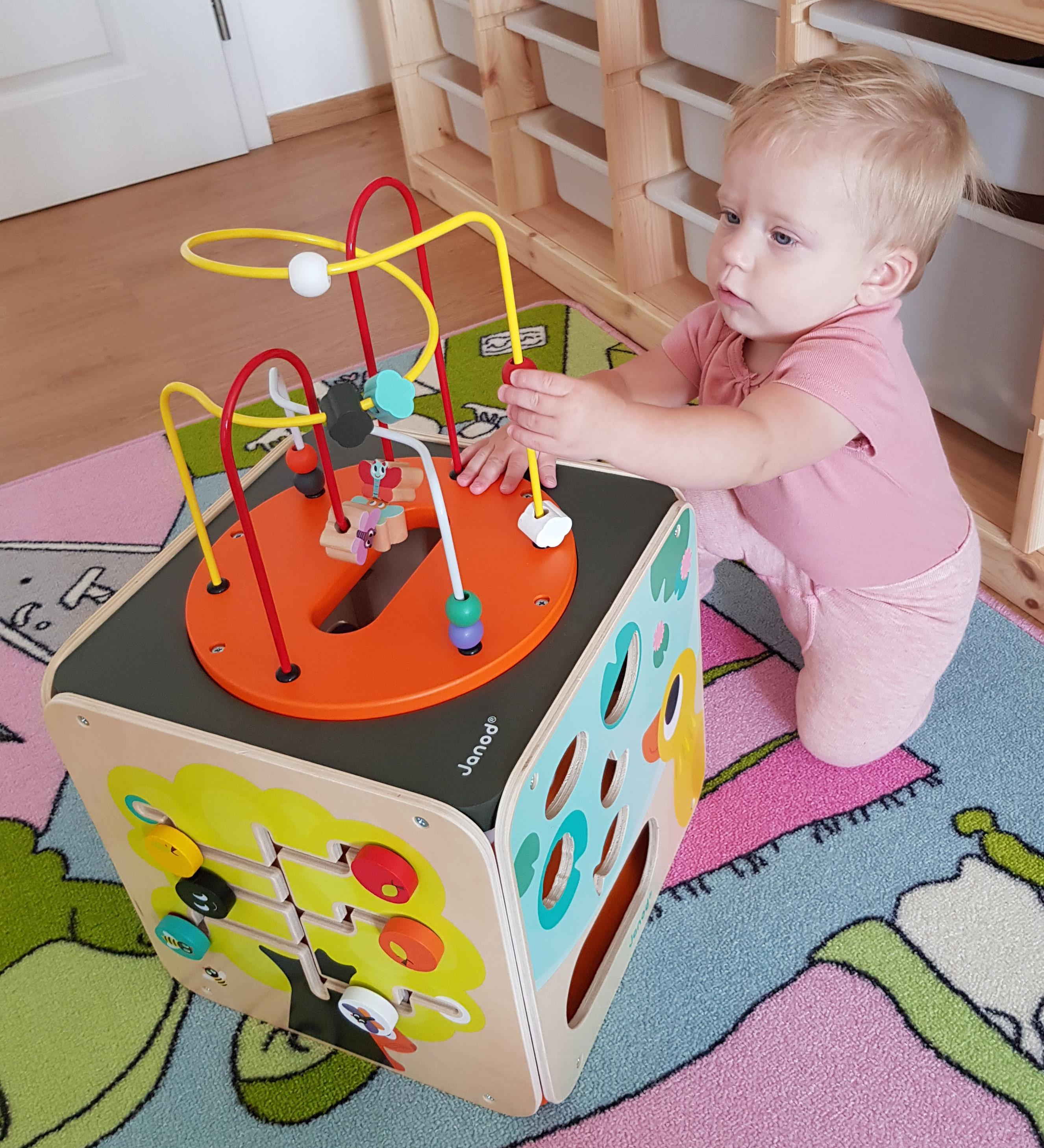 Dítě hrající si s dřevěnou didaktickou kostkou s labyrintem od Janod