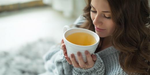 Žena hřející se s šálkem čaje v ruce