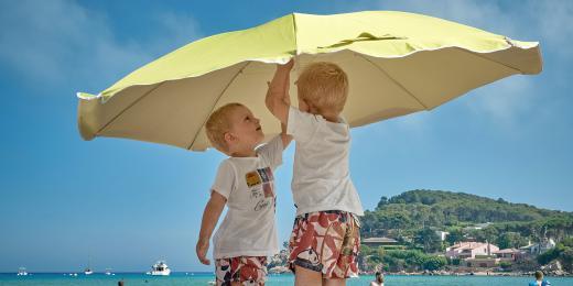 Malé děti stavějící slunečník na pláži