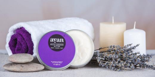 Ayan levandulové máslo na stole se svíčkami, levandulí, ručkníkem a kameny