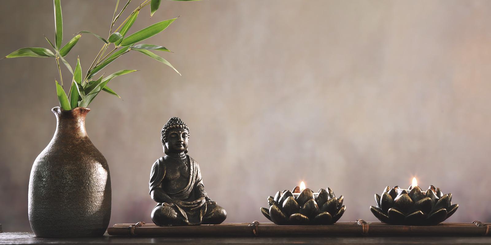 Buddha soška s rostlinnou a svíčkami